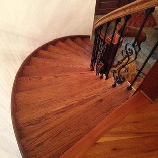 Immagine di un'ampia scala curva chic con pedata in legno, alzata in legno e parapetto in legno