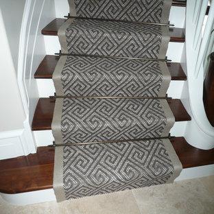 Ejemplo de escalera curva, clásica, de tamaño medio, con escalones de madera y contrahuellas de madera pintada