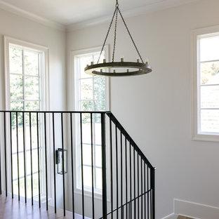 Ejemplo de escalera en L, tradicional renovada, de tamaño medio, con escalones enmoquetados, contrahuellas de madera pintada y barandilla de metal