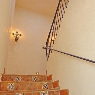 Ejemplo de escalera en U, mediterránea, grande, con escalones de terracota, contrahuellas de terracota y barandilla de metal