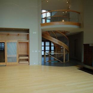 Esempio di un'ampia scala a chiocciola design con pedata in legno e nessuna alzata