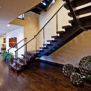 Foto de escalera suspendida, contemporánea, grande, con escalones de madera, contrahuellas de madera y barandilla de varios materiales