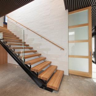 Ejemplo de escalera suspendida, contemporánea, grande, sin contrahuella, con escalones de madera y barandilla de vidrio