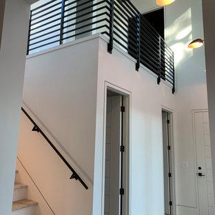 """Immagine di una scala a """"U"""" minimalista con pedata in travertino, alzata in legno e parapetto in metallo"""