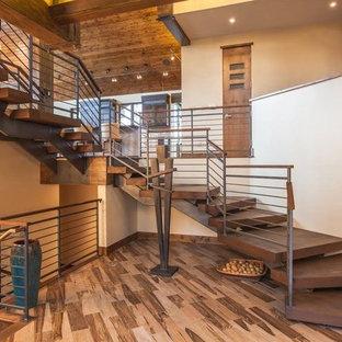 Foto de escalera curva, rústica, de tamaño medio, sin contrahuella, con escalones de madera y barandilla de cable