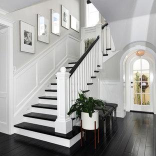 Foto de escalera en L, tradicional, de tamaño medio, con escalones de madera y contrahuellas de madera