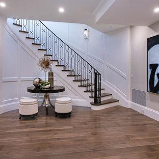 Immagine di una grande scala curva design con pedata in legno e alzata in legno