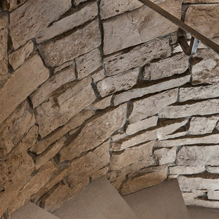 Foto di una grande scala a chiocciola tradizionale con pedata in cemento, parapetto in metallo e alzata in cemento
