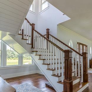 Immagine di una grande scala sospesa con pedata in legno, alzata in legno, parapetto in legno e pareti in perlinato