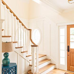 Ejemplo de escalera en L, tradicional, de tamaño medio, con escalones de madera y contrahuellas de madera pintada