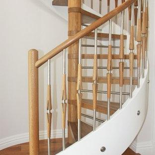 Immagine di una scala a chiocciola chic con pedata in legno e nessuna alzata