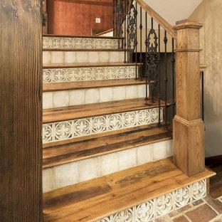 Foto de escalera en U, rústica, de tamaño medio, con escalones de madera, contrahuellas con baldosas y/o azulejos y barandilla de metal
