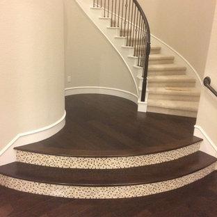 Modelo de escalera curva, clásica renovada, grande, con escalones de madera, contrahuellas con baldosas y/o azulejos y barandilla de metal
