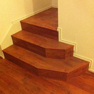 Ejemplo de escalera curva, clásica, de tamaño medio, con escalones de madera, contrahuellas de madera y barandilla de madera