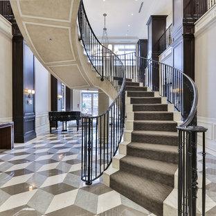 トロントの中サイズのタイルのトランジショナルスタイルのおしゃれなサーキュラー階段 (タイルの蹴込み板、金属の手すり) の写真