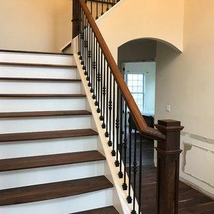Ejemplo de escalera en L, tradicional renovada, grande, con escalones de madera pintada, contrahuellas de madera y barandilla de varios materiales
