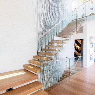 Пример оригинального дизайна: большая угловая лестница в современном стиле с деревянными ступенями, стеклянными подступенками и стеклянными перилами