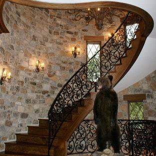 Diseño de escalera curva, mediterránea, con escalones de madera y contrahuellas de metal