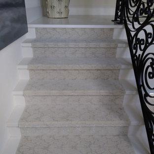 Imagen de escalera en L, contemporánea, grande, con escalones de mármol, contrahuellas de mármol y barandilla de metal