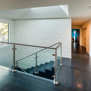 """Immagine di una scala a """"U"""" minimal di medie dimensioni con pedata in legno, alzata in vetro e parapetto in metallo"""