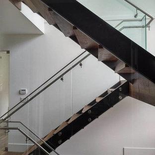 Exempel på en mellanstor modern flytande trappa i trä, med öppna sättsteg och räcke i metall