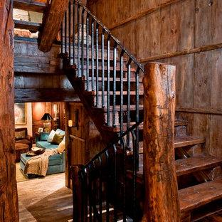 Imagen de escalera en U, rural, con escalones de madera, contrahuellas de madera y barandilla de metal