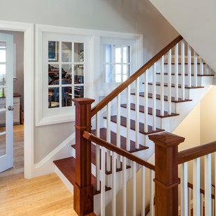Example of a large classic wooden u-shaped staircase design in Portland Maine with painted risers