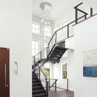 Ispirazione per un'ampia scala sospesa minimalista con pedata in legno verniciato e alzata in metallo