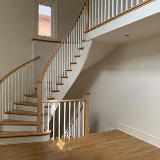 Ispirazione per una grande scala curva moderna con pedata in legno, alzata in legno verniciato e parapetto in legno