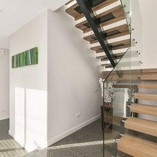 ウェリントンの大きい木のコンテンポラリースタイルのおしゃれな折り返し階段 (ガラスの蹴込み板) の写真