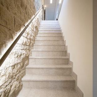 Imagen de escalera recta, moderna, de tamaño medio, con escalones de travertino, contrahuellas de travertino y barandilla de varios materiales