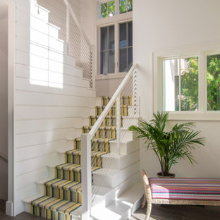 Staircase - beach style painted u-shaped staircase idea in Detroit with painted risers