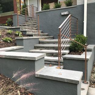 Cette photo montre un escalier tendance en L de taille moyenne avec des marches en pierre calcaire, des contremarches en béton et un garde-corps en métal.