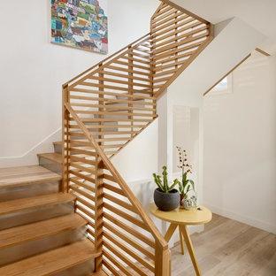 Ejemplo de escalera en U, actual, de tamaño medio, con escalones de madera, contrahuellas de metal y barandilla de madera