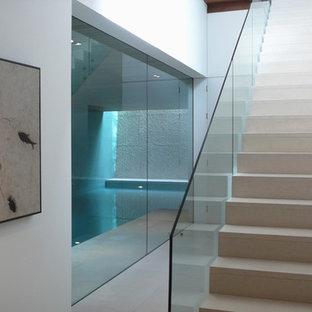Modelo de escalera en L, actual, de tamaño medio, con escalones con baldosas, contrahuellas de vidrio y barandilla de vidrio