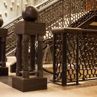 Imagen de escalera en U, clásica renovada, grande, con escalones de travertino, contrahuellas de travertino y barandilla de metal