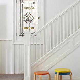 Modelo de escalera en L, nórdica, de tamaño medio, con barandilla de madera, escalones enmoquetados y contrahuellas enmoquetadas