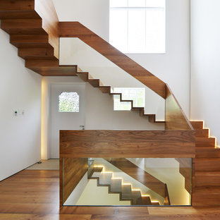 Design ideas for a large contemporary wood u-shaped staircase in London with wood risers.