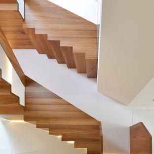 Foto de escalera en U, actual, grande, con escalones de madera y contrahuellas de madera