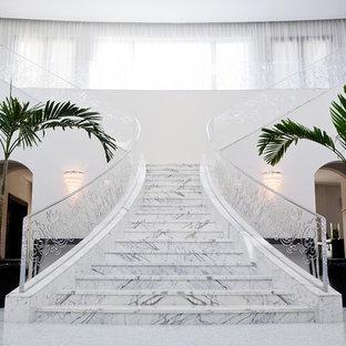 Foto de escalera en L, actual, con escalones de mármol, contrahuellas de mármol y barandilla de metal