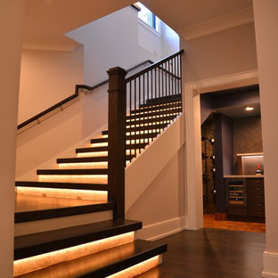 Example of a huge wooden u-shaped staircase design in Chicago with glass risers