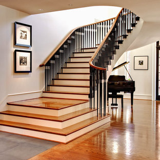 Classic wood curved staircase in Charlotte with painted wood risers.