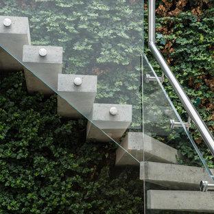 Imagen de escalera curva, contemporánea, sin contrahuella, con escalones de hormigón y barandilla de vidrio
