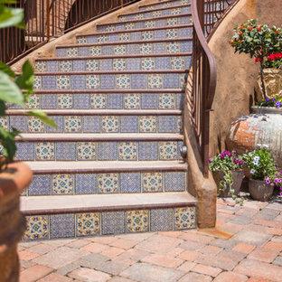 Diseño de escalera curva, mediterránea, grande, con escalones de hormigón, contrahuellas con baldosas y/o azulejos y barandilla de metal