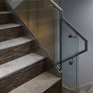 Diseño de escalera en U, de tamaño medio, con escalones de mármol, contrahuellas con baldosas y/o azulejos y barandilla de vidrio