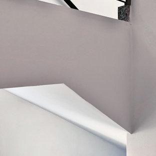 Réalisation d'un grand escalier droit minimaliste avec des marches en carrelage, des contremarches en carrelage, un garde-corps en verre et un mur en parement de brique.