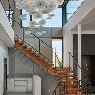 Imagen de escalera en L, actual, sin contrahuella, con escalones de madera y barandilla de metal
