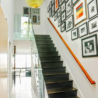 Trendy painted straight glass railing staircase photo in San Francisco with wooden risers