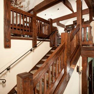 デンバーのスレートのラスティックスタイルのおしゃれな折り返し階段 (木の蹴込み板、木材の手すり) の写真