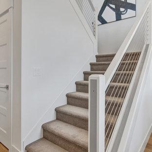 ポートランドの中サイズのカーペット敷きのコンテンポラリースタイルのおしゃれな折り返し階段 (カーペット張りの蹴込み板、ワイヤーの手すり) の写真